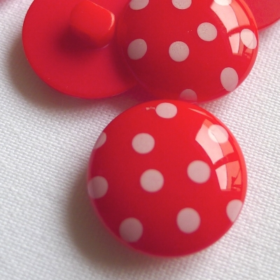 Red polyester button with white dots