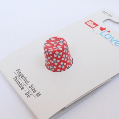 Red thimble with blue and white dots
