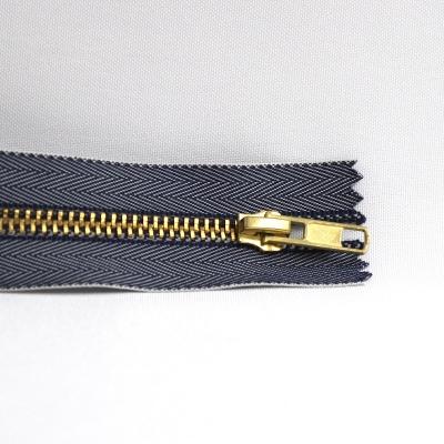Fermeture éclair métal or et jeans bleu