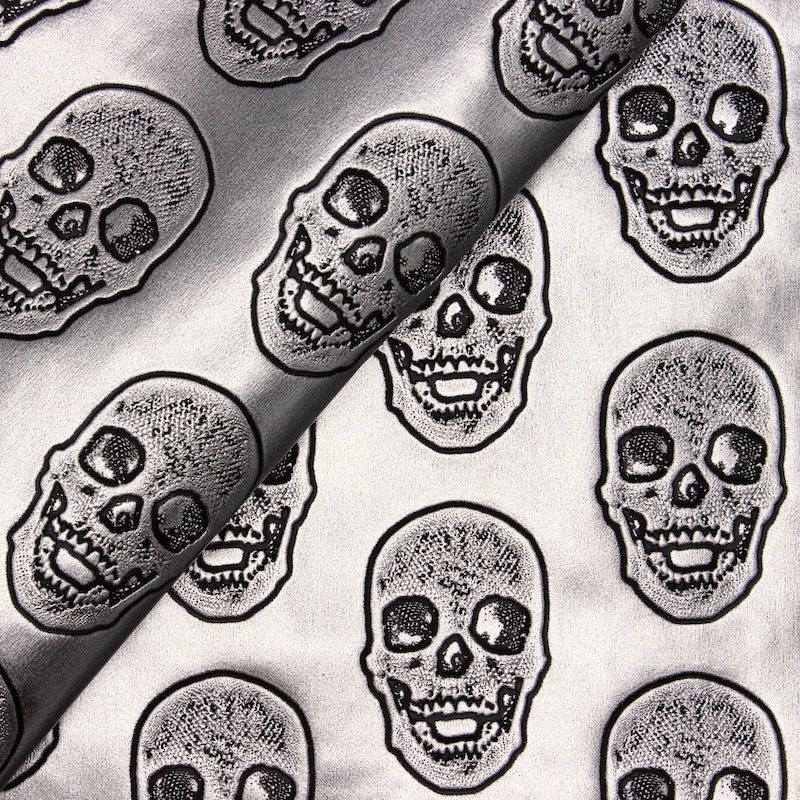 Imitatieleer met doodskoppen op een zilverkleurige achtergrond