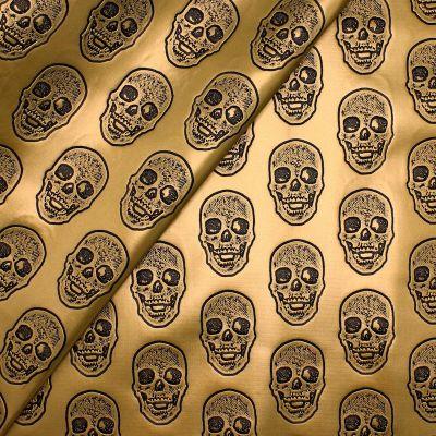 Simili cuir doré à têtes de mort