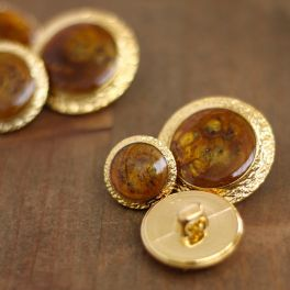 Button with metal and amber aspect