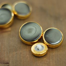 Button with golden metal and verdigris aspect