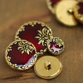 Round resin button with golden metal and enamelled red