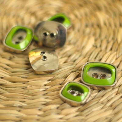 Button with silver metal and olive green aspect