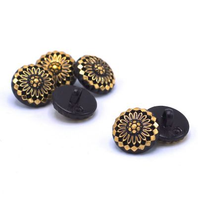 Round button with golden metal and black aspect