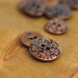 Resin button with carved flower pattern
