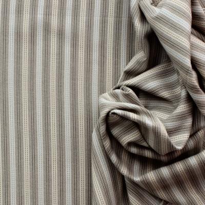 Tissu en coton à lignes vert et bleu sur fond beige