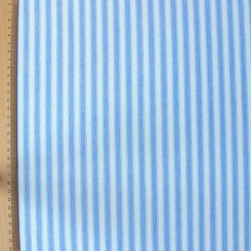 Katoenstof blauw gestreept op een lichtblauwe achtergrond