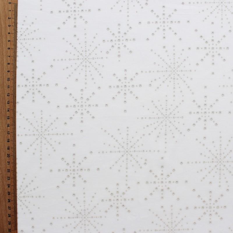 Katoen stof met beige sterrenmotief op witte achtergrond